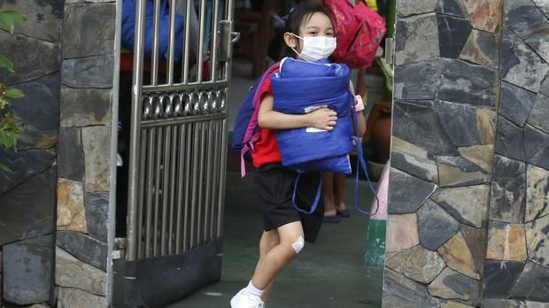 Pupils wear protective masks due to the high levels of city air pollution (Sakchai Lalit/AP)
