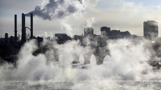 Water vapour rises above St Anthony Falls on the Mississippi River as the Stone Arch Bridge is obscured, seen from the Third Avenue Bridge in Minneapolis (David Joles/Star-Tribune/AP)