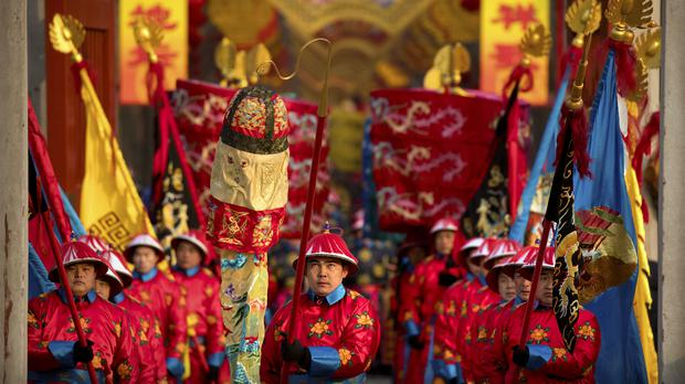Performers carry flags during a Qing Dynasty ceremony in Ditan Park in Beijing (AP Photo/Mark Schiefelbein)