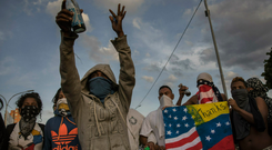 FLASHPOINT: Anti-government protesters in Venezuela — with unlit petrol bombs in their hands — blocking a highway in Caracas. Photo: AP/Rodrigo Abd