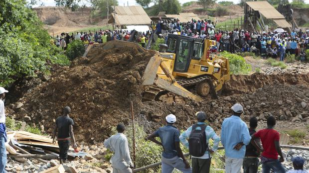 Heavy machinery is used to clear the ground as rescuers bid to reach trapped gold miners (Tsvangirayi Mukwazhi/AP)