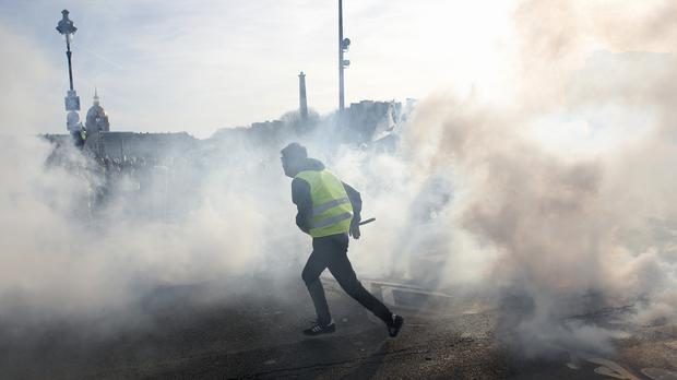 A yellow vest protester runs amid tear gas during scuffles with riot police officers in Paris (AP)