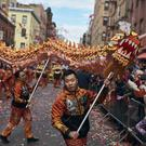 A member of a dance group carries the head of the dragon during the Chinese Lunar New Year parade in Chinatown in New York (Andres Kudacki/AP)