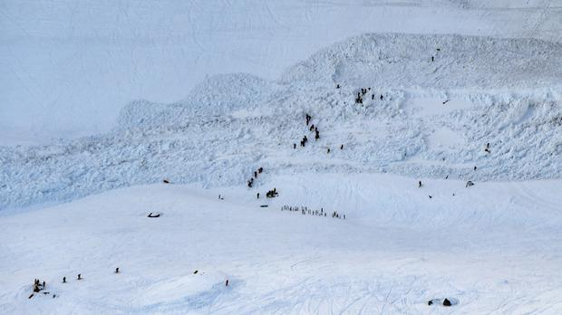Rescue crews work on the avalanche site at the ski resort of Crans-Montana, Switzerland (Anthony Anex/Keystone via AP)