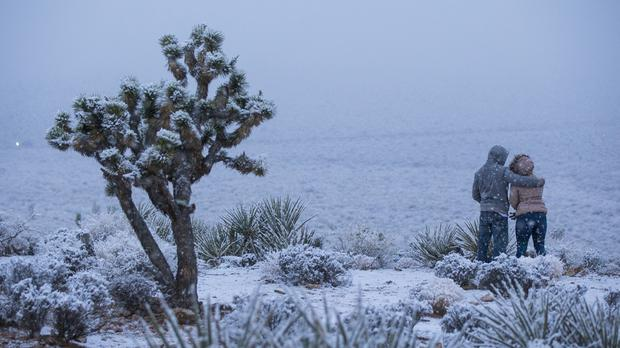 A couple watch as snow falls around the overlook at the Red Rock Canyon National Conservation Area outside of Las Vegas (Chase Stevens/Las Vegas Review-Journal via AP)