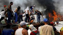 Opposition supporters unload a truck set on fire at Francisco de Paula Santander bridge on the border between Colombia and Venezuelaago. Photo: Reuters