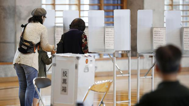 People prepare to vote in a referendum at a polling station (Kyodo News/AP)