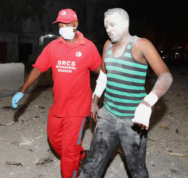 A man injured in the Somali capital is helped away