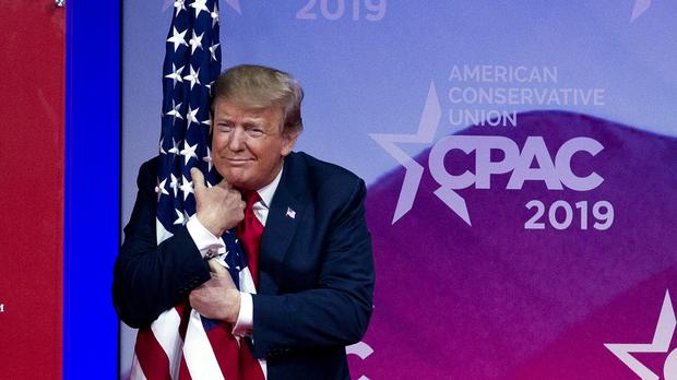 President Donald Trump hugs the American flag (Jose Luis Magana/AP)