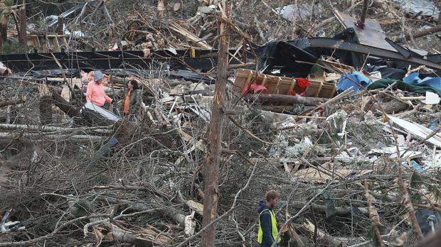 Two women and a man stand in the wreckage of homes as rescue workers work through the debris in Beauregard, Alabama (Curtis Compton/Atlanta Journal-Constitution via AP)