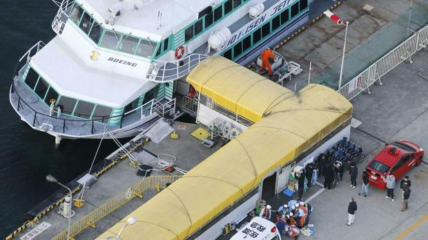 Firefighters prepare to taken injured passengers to a hospital at a port in Sado city (Kyodo News via AP)