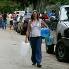 A woman carries containers to collect water from a fountain in the wake of shortages. Photo: AP
