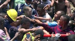 People help a child after he was rescued from the scene of a building collapse in Lagos (AP)