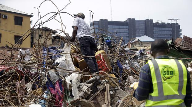Government officials examine materials used in constructing the building that collapsed in Lagos, Nigeria (Sunday Alamba/AP)