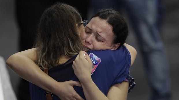 Relatives embrace during a wake for the victims of a school shooting in Brazil (Andre Penner/AP)