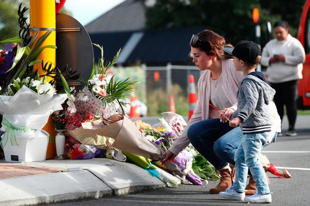 Trauma: People lay flowers outside a mosque in central Christchurch, New Zealand, yesterday as they come to terms with the senseless killings of 49 people. Photo: Mark Baker/AP
