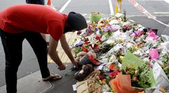 A man places flowers at a makeshift memorial near the Masjid Al Noor mosque in Christchurch, (Mark Baker/AP)