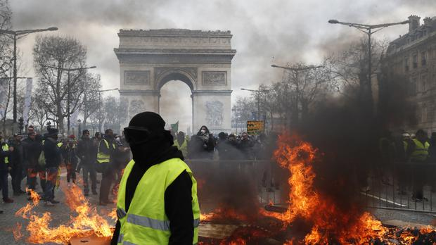 A yellow vest protester walks past a fire on the Champs Elysees (AP)