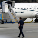 Grounded: A worker walks next to a Boeing 737 MAX 8 plane parked at Boeing Field in Seattle. US.