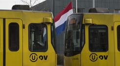 A tram passes a Dutch flag flying half-staff (AP Photo/Peter Dejong)