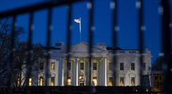 The White House is seen through a security fence, before sunrise, in Washington DC (Cliff Owen/PA)