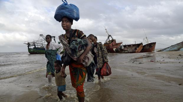 A displaced family arrives after being rescued by a boat from a flooded area of Buzi district (AP)