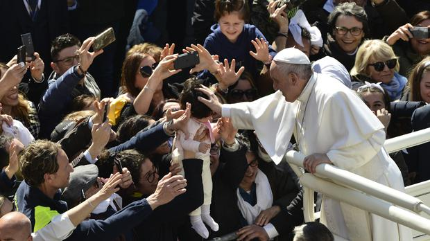 Faithful hand a baby to Pope Francis to bless upon his arrival at Loreto's cathedral (Sandro Perozzi/AP)