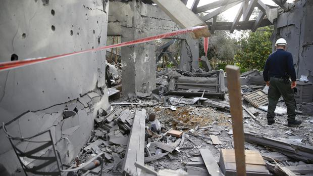 A police officer inspects the damage to a house hit by a rocket in Mishmeret, central Israel (Ariel Schalit/AP)