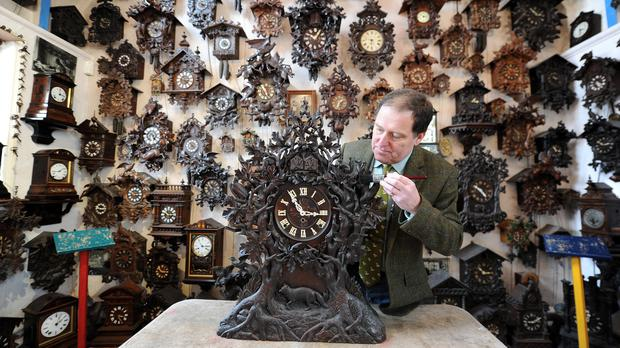 Roman Piekarski makes a start to changing the time on one of more than 600 cuckoo clocks at his Cuckooland Museum in Tabley, Cheshire (Martin Rickett/PA)