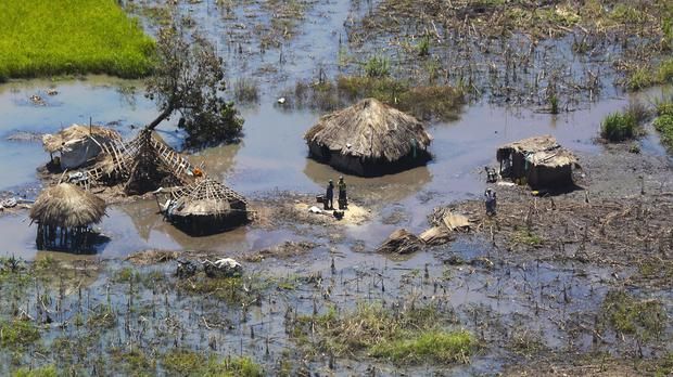 A family stands outside their submerged huts near Beira, Mozambique (Tsvangirai Mukwazhi/AP)