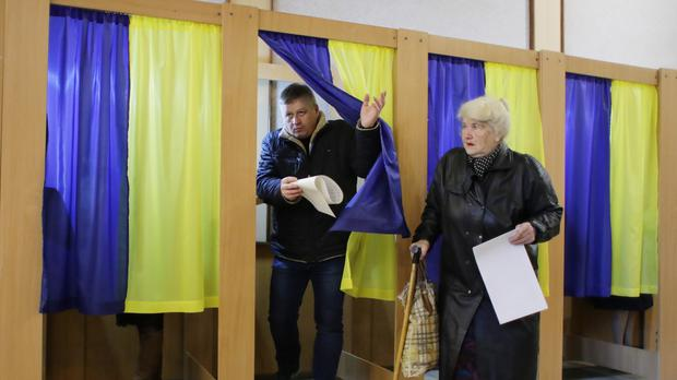 People hold their ballots before casting votes at a polling station (Sergei Grits/PA)