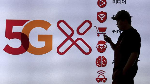 A man passes by a banner advertising 5G networks in Seoul (Ahn Young-joon/AP)