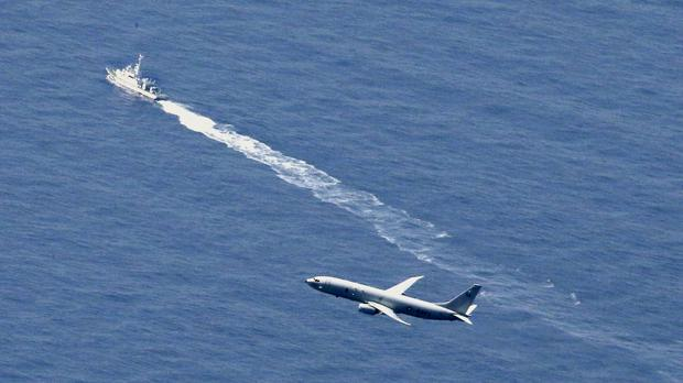 A Japan Coast Guard vessel and US military plane search for the Japanese fighter jet (Kyodo News via AP/PA)