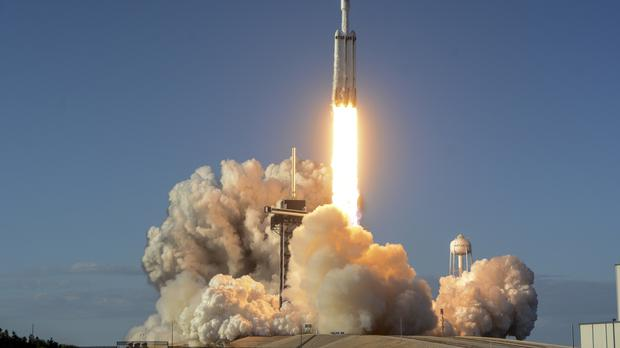 A SpaceX Falcon Heavy rocket carrying a communication satellite lifts off (Craig Bailey/Florida Today via AP)