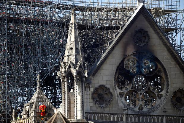 Charred: A firefighter makes his way on a balcony of the damaged Notre-Dame Cathedral yesterday. Photo: Francois Mori/AP
