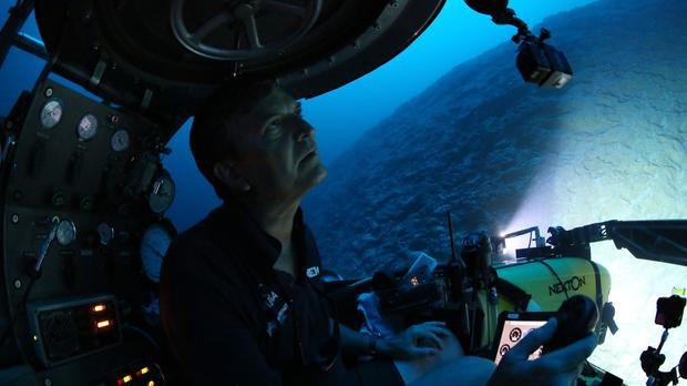 Pilot Robert Carmichael looks out of a submersible as he navigates strong currents during a dive below the surface of the ocean (David Keyton/AP)