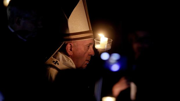 Pope Francis holds a candle as he presides over a solemn Easter ceremony (Gregorio Borgia/AP)