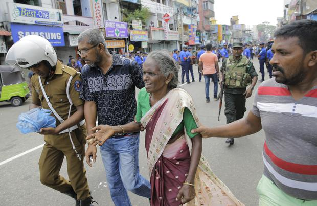 An elderly woman is helped near St Anthony's Shrine in Colombo (Eranga Jayawardena/AP)