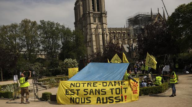 People fix a banner that reads in French: 'Notre-Dame is roofless, we too!' (Francisco Seco/AP)