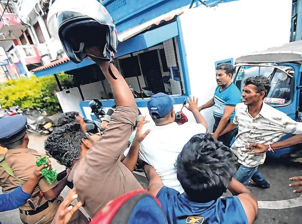 Anger: People try to beat a person held by police near a church in Colombo, Sri Lanka. Photo: Reuters/Dinuka Liyanawatte