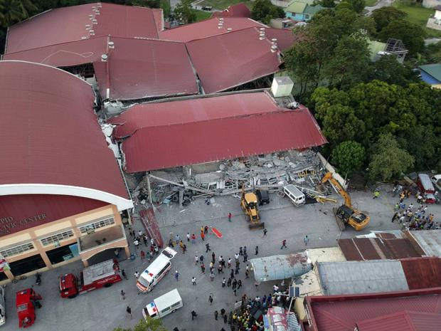 Workers use heavy equipment to clear an area as rescue efforts continue for people still trapped (AP Photo/Vhic Y Naluz)
