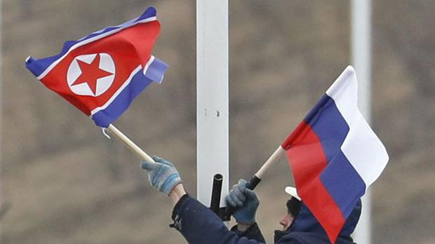 A worker adjusts the flag of Russia and North Korea along the road in Russky Island, off the southern tip of Vladivostok (Naoya Osato/AP)