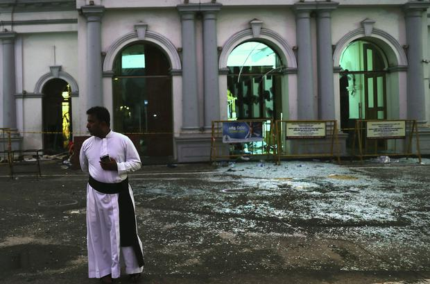 A Sri Lankan catholic priest stands near broken glass in front St Anthony's Church in Colombo (Manish Swarup/AP)