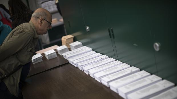 A man inspects the ballot papers at a polling station (Emilio Morenatti/AP)