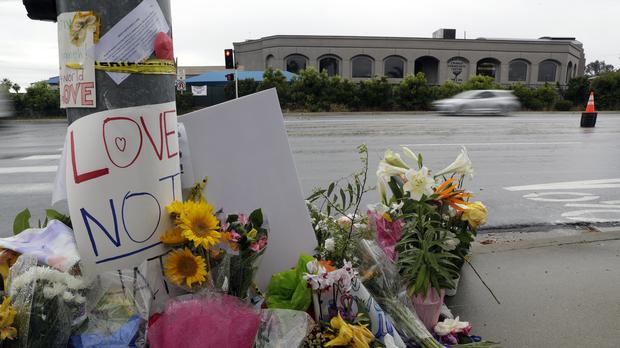 Signs of support and flowers adorn a post in front of the Chabad of Poway synagogue (Gregory Bull/AP)