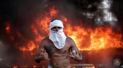 Fire on the streets: A supporter of Juan Guaidó arms himself with a stone in front of a burning bus near Caracas