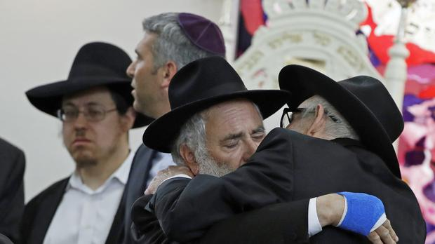 Rabbi Yishoel Goldstein, centre, hugs an attendee at the funeral for Lori Kaye, who was killed Saturday when a gunman opened fire inside the Chabad of Poway synagogue in Poway, California (Gregory Bull/AP)