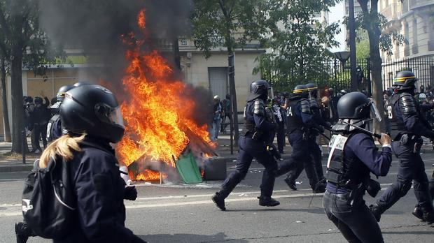 Police officers pass by burning rubbish as they confront demonstrators (Francois Mori/AP)