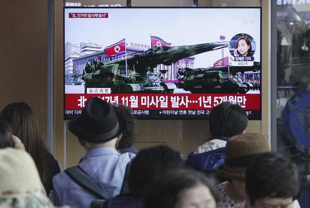 People watch a TV showing file footage of North Korea's missiles during a military parade in Pyongyang (Ahn Young-joon/AP)