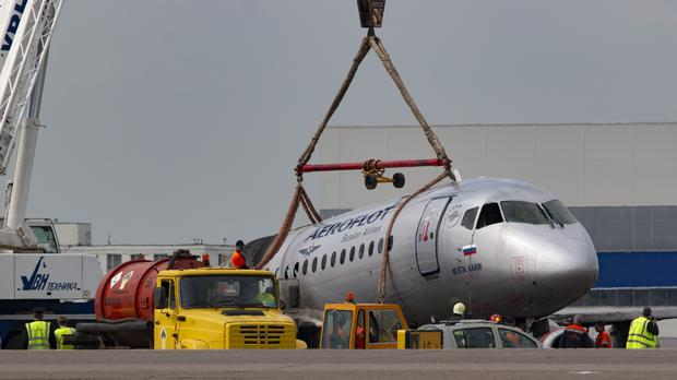 A crane lifts the damaged aircraft (AP)